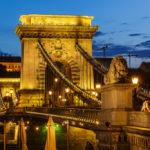 Beleuchtete Kettenbrücke nach Sonnenuntergang in der blauen Stunde