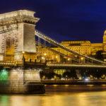 Beleuchtete Kettenbrücke und Burgpalast nach Sonnenuntergang in der blauen Stunde
