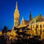 Blick von der Fischerbastei aus auf die beleuchtete Matthiaskirche nach Sonnenuntergang in der blauen Stunde
