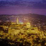 Blick vom Gellértberg auf den beleuchteten Burgpalast nach Sonnenuntergang in der blauen Stunde