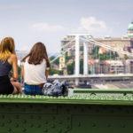 Zwei Mädchen sitzen auf dem Pfeiler der Freiheitsbrücke und genießen die Aussicht auf die Burg und die Elisabethbrücke