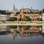 Blick auf die Fischerbastei, Matthiaskirche und Calvinistische Kirche in Budapest mit Spiegelung