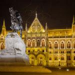 Außenansicht des Parlaments in der Nacht mit Vogelschwarm über dem Gebäude