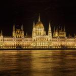 Außenansicht des Parlaments von Budapest in der Nacht mit Vogelschwarm über dem Gebäude