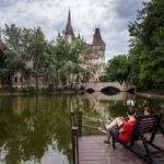 Zwei Burschen entspannen der der Spiegelung der Burg Vajdahunyad im Stadtwäldchen