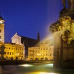 Beleuchteter Samsonbrunnen und historische Gebäude auf dem Marktplatz von Budweis