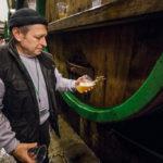 Ein Braumeister zapft direkt vom Fass in der Brauerei Pilsner Urquell