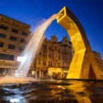 Beleuchtete historische Häuserzeile und ein goldener Brunnen auf dem Hauptplatz