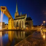 Beleuchtete St.-Bartholomäus-Kathedrale und ein goldener Brunnen auf dem Hauptplatz