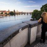 Eine junge Frau blickt von der Brücke Mánesův Most in Richtung Karlsbrücke (Karlův most)