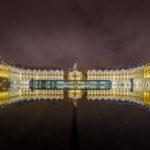 Die Gebäude auf dem Place de la Bourse spiegeln sich in regnerischem Wetter im Miroir d'Eau