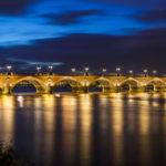 Die beleuchtete Brücke Pont de Pierre spiegelt sich in der Garonne