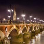 Die beleuchtete Brücke Pont de Pierre, dahinter der Glockenturm der Basilika Saint Michel