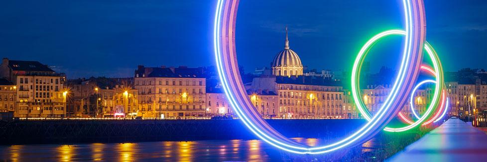Blick durch die leuchtenden Ringe auf die Altstadt mit der Basilika Église Notre-Dame-de-Bon-Port