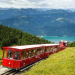 Die Schafbergbahn auf offener Strecke, dahinter der Wolfgangsee