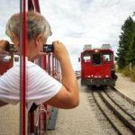 Ein Tourist fotografiert die Schafbergbahn an einer Ausweichstelle