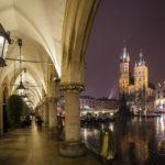 Blick auf die beleuchtete Marienkirche von den Arkaden der Tuchhallen