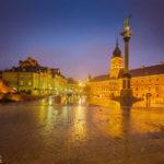 Das beleuchtete Warschauer Königsschloss und die Sigismundssäule spiegeln sich auf dem nassen Boden