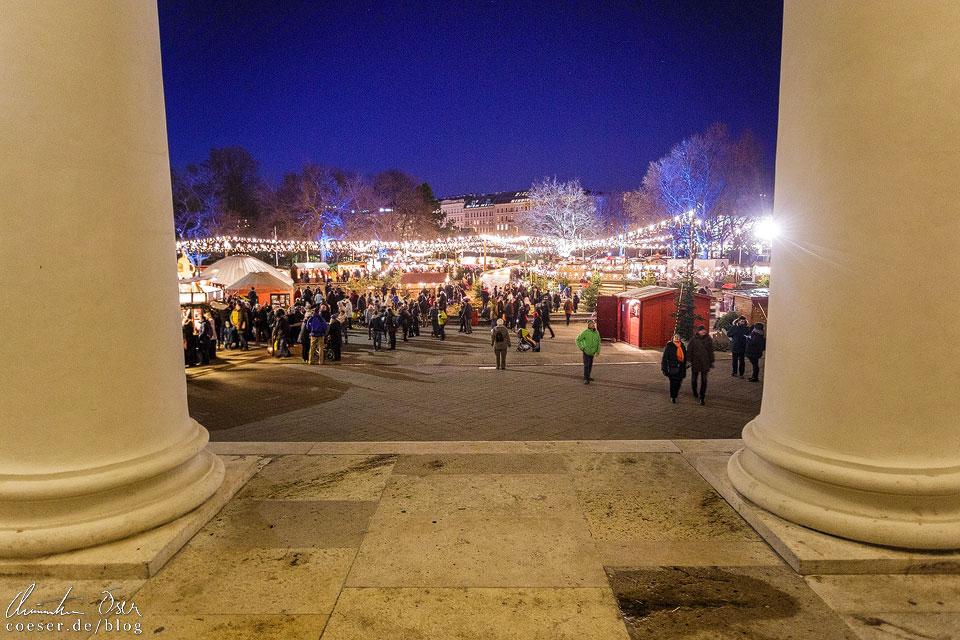 Blick auf den Adventmarkt Karlsplatz zwischen den Säulen der Karlskirche