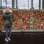 Ein Mädchen befestigt ein Liebesschloss an der Hohenzollernbrücke