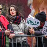 Eine Karnevalsbesucherin buhlt mit einem Kamelle-Schild um Aufmerksamkeit