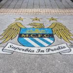 Das Logo von Manchester City vor dem Eingang des Etihad Stadium