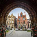 Eingangsbogen der Manchester Cathedral mit Blick auf historische Gebäude