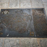 Eine Eisenplatte im Gehsteig mit den Umrissen der Altstadt von Toledo