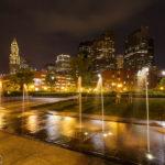 Wasserspiele in einem Park auf der Waterfront mit Blick auf den Custom House Tower und die Skyline von Boston bei Nacht