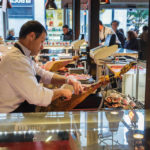 Ein Verkäufer schneidet Schinken (Jamón) in der Markthalle San Miguel (Mercado San Miguel) in Madrid