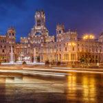 Der Palacio de Cibeles und der Cibeles-Brunnen (Fuente de Cibeles) in Madrid in der blauen Stunde während eines Regenschauers