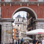 Blick durch ein Zugangstor des Hauptplatzes (Plaza Mayor) von Madrid auf die Stiftskirche San Isidro (Iglesia de San Isidro)