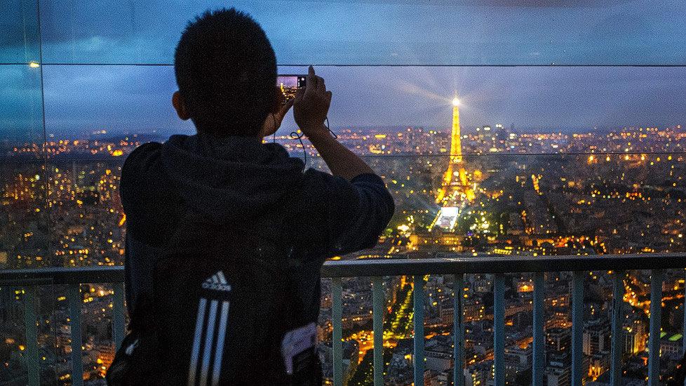 Ein Tourist fotografiert auf der Aussichtsterrasse des Tour Montparnasse in Richtung Eiffelturm