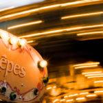 Ein Crêpe-Stand mit Karussell vor dem Tour Montparnasse in Paris
