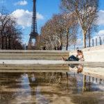 Ein Pärchen entspannt vor dem Eiffelturm im Park Champ de Mars