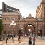 Spaziergänger auf der Straße Riksgatan mit Blick auf den bogenförmigen Durchgang des Reichstags (Riksdagshuset)