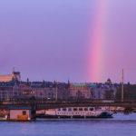 Ein Regenbogen und die untergehende Sonne in der Ferne tauchen Stockholm in ein magisches Licht