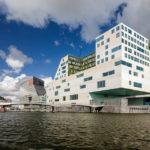 Hinter dem Hauptbahnhof sieht man vom Boot aus moderne Gebäude wie den Justizpalast im Gebäudekomplex IJdock