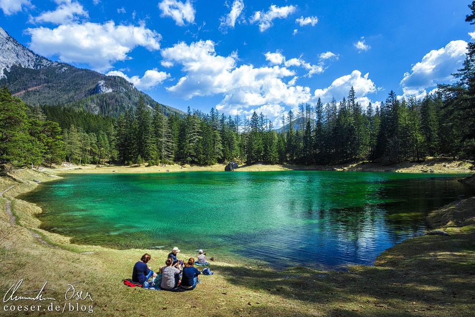 Touristen sitzen am Ufer des Grünen Sees Tragöß