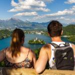 Ein junges Paar genießt den Blick auf den Bleder See vom Aussichtspunkt Ojstrica