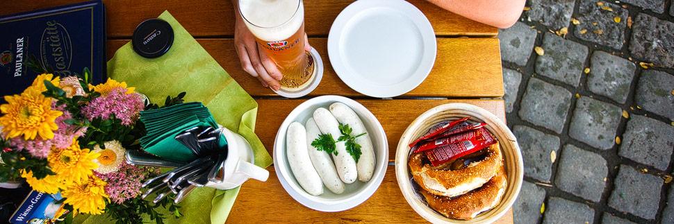 Weißwurst und Weißbier in einem Biergarten in München