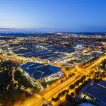 Blick vom Olympiaturm auf die BMW-Welt, den BMW-Vierzylinder und das BMW-Werksgelände während der Blauen Stunde