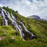 Ein schöner Wasserfall mit dem Old Man of Storr als Hintergrundmotiv
