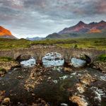 Die Sligachan Old Bridge mit dem Black-Cuillin-Bergmassiv im letzten Sonnenlicht