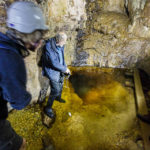 Der Führer zeigt ein überschwemmtes Loch, das den unterirdischen Zugang zu einer weiteren Höhle darstellt