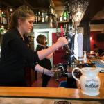 Eine Kellnerin zapft ein Pint im The Clachan Pub in Dornie