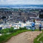 Touristen genießen von Arthur's Seat aus das Panorama der Stadt Edinburgh