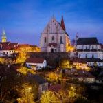 Blick vom Burgareal auf die beleuchtete Altstadt von Znaim mit der St.-Nikolaus-Kirche und dem Rathausturm