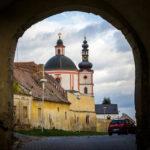 Blick durch einen Torbogen auf die Kirche des Heiligen Hippolyt und das Kloster der Kreuzherren mit dem Roten Stern auf dem Pöltenberg