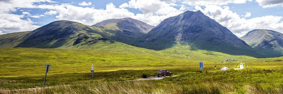 Autos auf einer einsamen Straße in Schottland